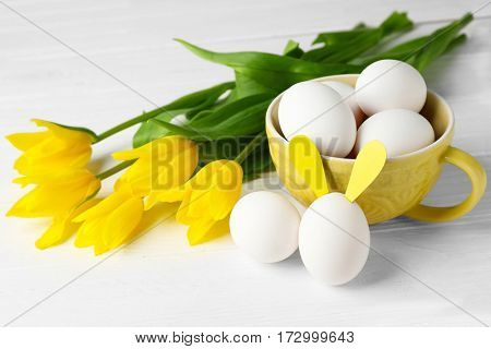 Easter eggs with bunny ears on white wooden table