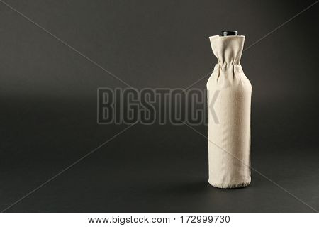 St. Valentine's Day concept. Wine bottle in gift linen pouch on dark background