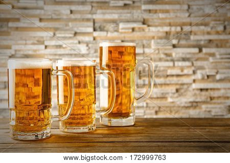 Mugs with beer on wooden table