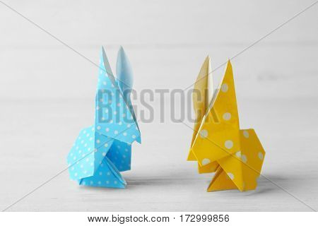Easter bunnies on wooden table against light background