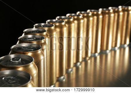 Cans of beer on table against black background