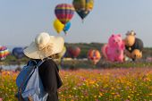 Woman tourist is traveling into Balloon festival in Chiangrai Provice Thailand. Woman traveller with white hat and bag standing looking beautiful balloon in cosmos flower field. poster