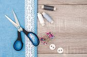 Jeans fabric for sewing lace and accessories for needlework on old wooden background. Spool of thread scissors buttons sewing supplies. Set for needlework top view poster