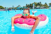 Tween girl relaxing on the inflatable ring in water in the aqua park in Thailand poster