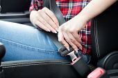 Close up of female hands fastening seat belt in car. Safety driving concept poster