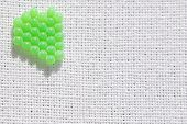 Macro view of aligned green eggs/ball on a white cotton linen. poster