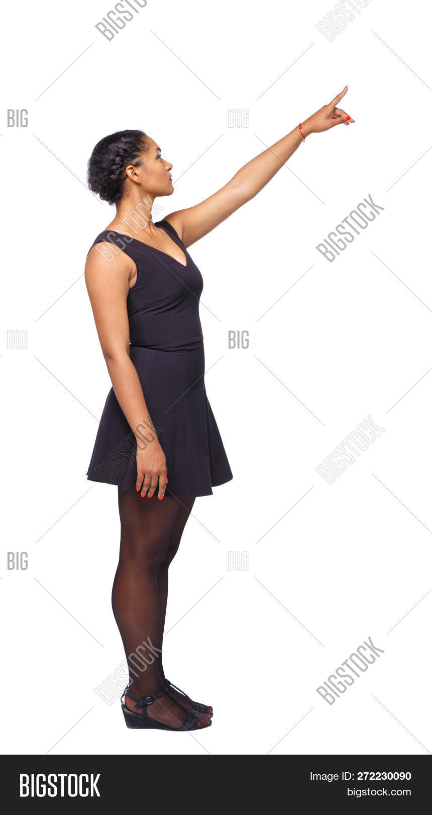 bac28876ed669 Side view of a black African-American woman in a brown dress pointing  upwards.