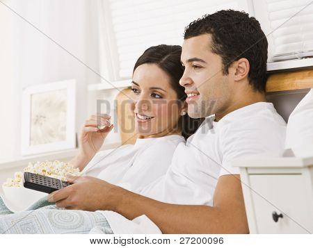 An attractive young couple lying in bed and watching television.  They have a bowl of popcorn and a remote. They are smiling. Horizontally framed photo.
