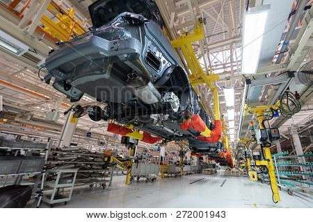 Transfer Of Car Body Bottom View. Robotic Equipment Makes The Assembly Of Car. Modern Car Assembly A