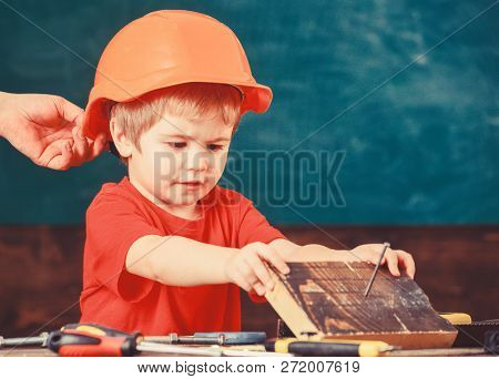Toddler In Protective Helmet At Workshop. Child Cute And Adorable Play With Wood And Screw While Mal