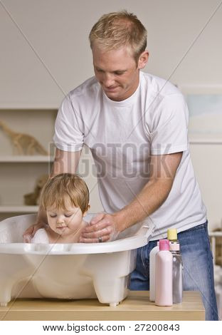 A young father is giving his baby daughter a bath in a childs tub.  He is smiling and looking down at his daughter.  Vertically framed shot.