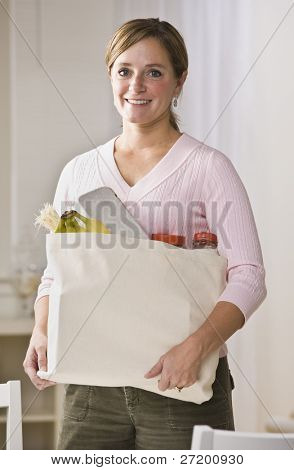 A woman is standing in her kitchen and holding a bag of groceries.  She is smiling at the camera.  Vertically framed shot.