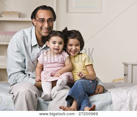 A father is sitting on a bed with his two young daughters.  They are smiling at the camera.  Horizontally framed shot.