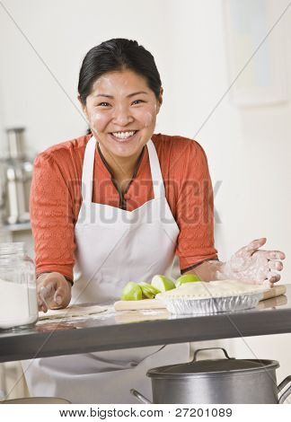 A woman is standing in a kitchen and slicing apples for a pie.  She is looking away from the camera.  Vertically framed shot.
