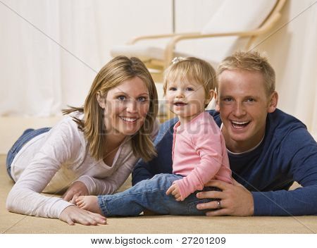 A beautiful and young couple pose with their young daughter as they all smile at the camera.  Horizontally framed shot.