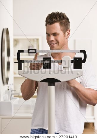 Attractive male weighing himself on scale and smiling. Vertical