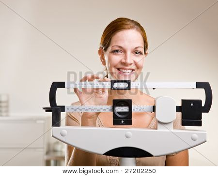 Woman weighing herself in doctor office
