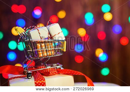 Shopping Cart With Christmas Box. Valentine's Gifts. Color Bokeh Background. Christmas Sales. Merry