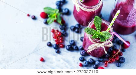 Flat-lay Of Colorful Smoothies In Bottles With Fresh Tropical Fruit And Superfoods On Concrete Backg