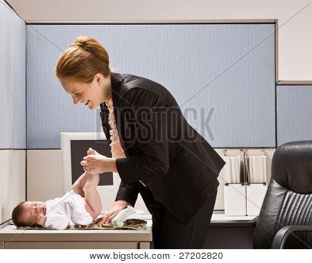 Zakenvrouw veranderen luier baby op Bureau