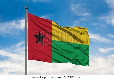 Flag Of Guinea Bissau Waving In The Wind Against White Cloudy Blue Sky. Guinean Flag.