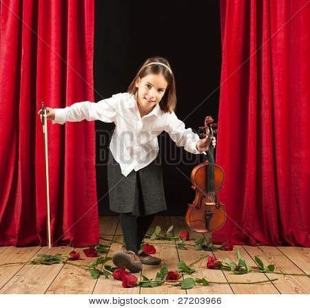 Little girl playing violin on stage theater