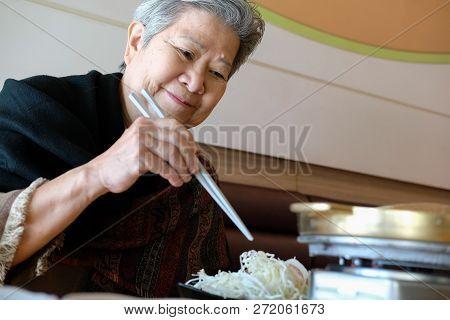 Old Elderly Elder Woman Eating Food In Restaurant. Senior Lifestyle