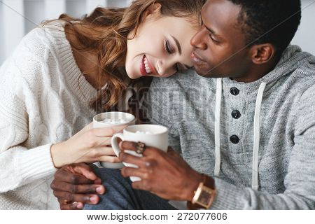 Happy Loving Couple Drinking Cocoa On A Winter Morning In Bed