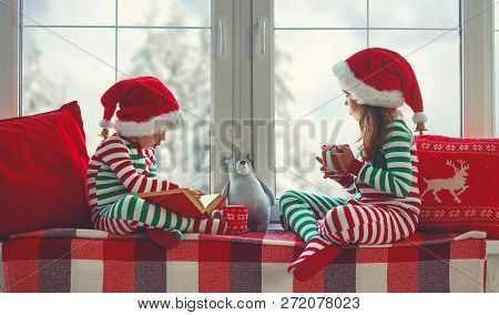 Children Girl And Boy In Pajamas Is Sad On Christmas Morning By The Window.