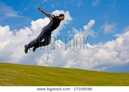 Man jump over meadow in mountains