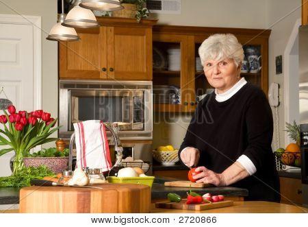 Mature Woman Cutting Tomato.