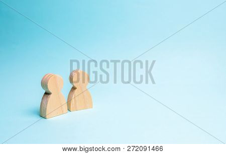 Two People Stand Together And Talk. Two Wooden Figures Of People Conduct A Conversation On A Blue Ba