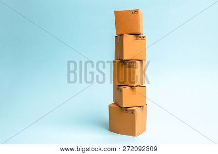 Tower Of Cardboard Boxes On A Blue Background. The Concept Of Moving And Delivery Of Goods And Goods