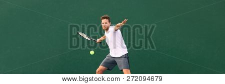 Tennis player man hitting ball with forehand hit on outdoor court playing game. Male sports athlete working out cardio traning. Panorama banner on green background.