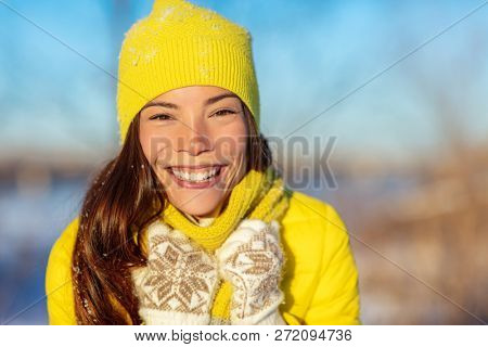 Winter Asian woman smiling in cold weather fashion accessories for winter: yellow hat and knit scarf, wool gloves, down jacket. Happy girl enjoying season outside.
