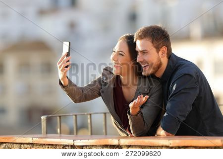 Happy Couple Having A Video Call Or Taking Selfies With A Smart Phone In A Balcony At Sunset