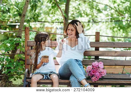 Mom And Her Little Daughter On A Bench In The Park.