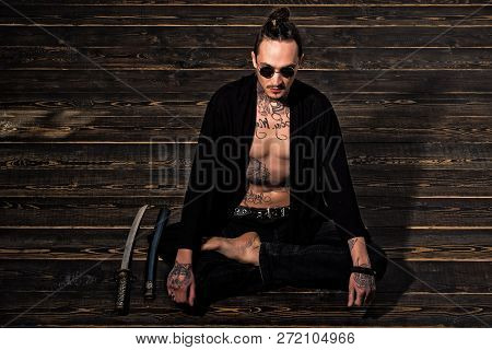Man With Tattooed Torso In Black Clothes Sitting In Meditation Pose With Swords On Wooden Floor. Zen
