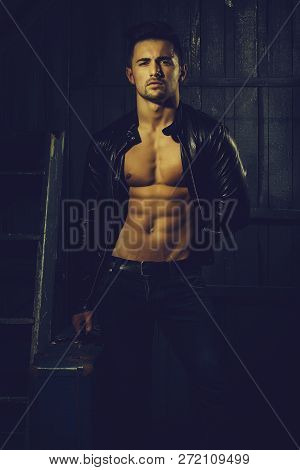 Handsome Sexy Sensual Muscular Stylish Young Man In Leather Jacket With Bare Torso Standing With Ret