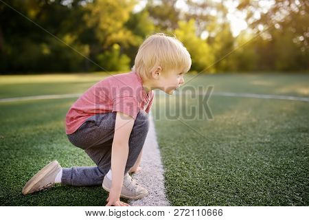 Little Boy Sportsman Getting Ready To Run A Distance At The School Stadium. Kids Sports.