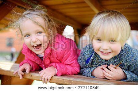 Happy Kids Having Fun On Outdoor Playground. Spring/summer/autumn Active Sport Leisure For Children.