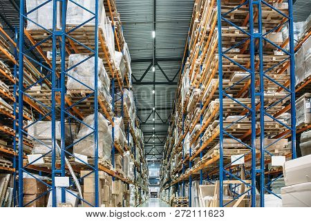 Large Logistics Hangar Warehouse With Lots Shelves Or Racks With Pallets Of Goods. Industrial Shippi