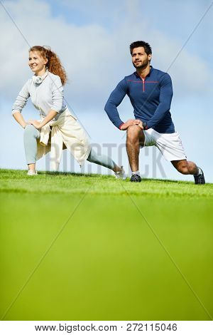 Healthy active young couple doing exercise for legs on green field in the morning