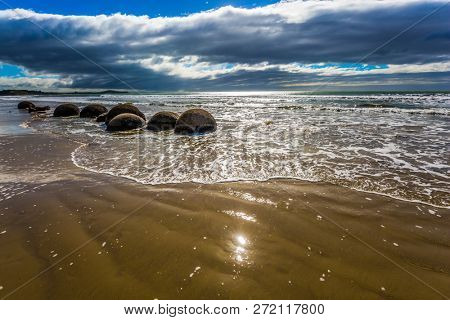 Boulders Moeraki -  large spherical boulders on the beach Koekokhe. Ocean evening tide. Travel to New Zealand. The concept of active, eco and photo tourism