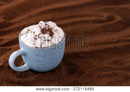 Closeup Of Tasty Coffee And Whipped Cream. Cup On A Table Covered With Ground Coffee