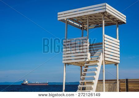 A White Lifeguard Tower Near The Ocean