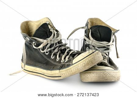 Old faded and worn sneakers isolated on white background