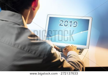 Businessman Using Laptop With Growing Financial Chart In 2019 On The Screen. Business Concept. Happy