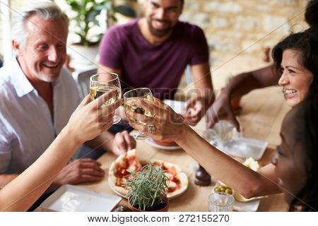 Friends laughing at a dining table in a cafe making a toast