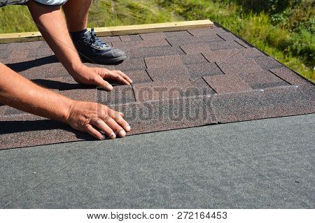 Roofer Hands Laying Asphalt Shingles On House Construction Roof. Roofing Construction With Asphalt S